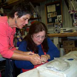pottery teacher hedy giving instruction on handbuilding to student at pottery class at full moon pottery studio located in Morro Bay, California
